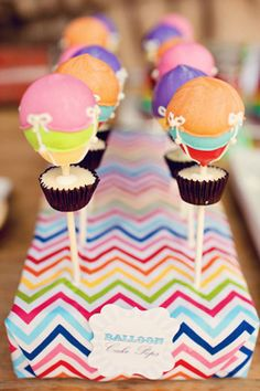 Michelle - the multi-colored cake pops are doable. We can dip in 3 different colors of your choice. Then piping the white would be simple :)....also, I have some foam we can wrap in corresponding paper to stick them in as it is in the photo. @Michelle Stevens