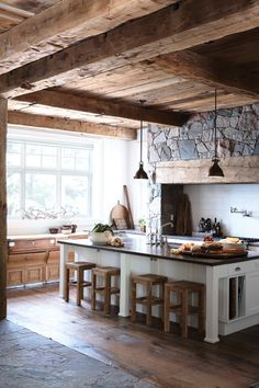 An earth friendly kitchen in stone, wood and tile.  The stone wall in this rustic kitchen is highlighted by salvaged wood beams and white tile. Floor made from flagstone and reclaimed hemlock wood mirrors the stone wall panel and timber ceiling.