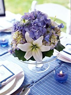 Wedding Centerpiece Ideas: Buttoned Up in Blue. A footed cake plate elevates this centerpiece to new heights. Blue votives burn in cups of blue sand, but colored sugar, pebbles, or beach glass would also look wonderful.