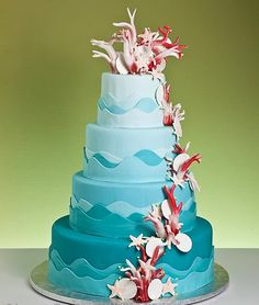 Unique, four tier aqua blue beach theme wedding cake. Decorated with light aqua blue and medium blue fondant, made to look just like the waves of the ocean