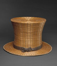 """Hat (Top), ca. 1820, French, raffia, silk  Height (crown): 7 3/4 in. (19.7 cm). Marking: [label] """"Melin, Poitiers"""". Men's top hats like this were worn primarily in the summer, most likely in the countryside while riding, hunting, promenading, or even playing cricket. (Source: Notable Acquisitions, 1984-1985, Metropolitan Museum of Art, page 37.)"""