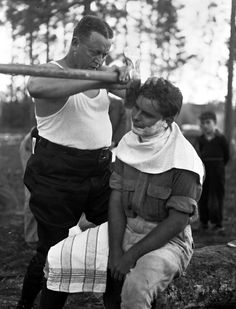One man shaves another man's face with an axe on forestry Field Day, 1940.