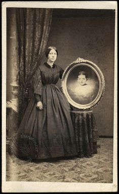 Woman in mourning clothing, posing with a memorial portrait of her little girl, surrounded by clouds.  Carte de visite, circa 1866