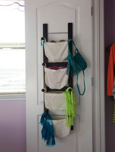 Inside closet doors are fair game for clever storage strategies like this mounted multi-bin storage rack loaded with grab-and-go accessories.