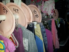 Garage sale organizing. Use paper plates to separate sizes on a clothing rack. Use pink for girls and blue for boys. Cut to the center and cut a big enough hole to fit on the rod.