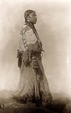 You are viewing an unusual image of Wishham Woman. It was taken in 1910 by Edward S. Curtis.    The image shows Chinook Indian from Tlakluit Washington. This shows a woman, full length, facing right, standing, wearing beaded buckskin dress.