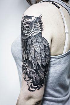 Black owl tattoo on upper arm. Beautiful linework.