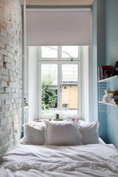 tiny bedroom. exposed brick wall painted white, white roller shade for window, white be linens, light blue painted walls