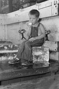 Summertime and a boy cools off on an ice truck. Boston 1937