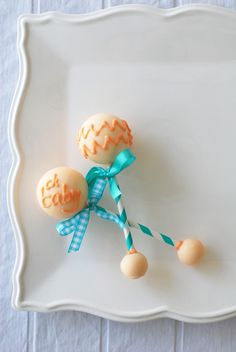 Cake Pop Rattles from the Chic Stork Baby Shower by WH Hostess. Aqua blue and coral color palette with classic baby accents like a stork, baby clothes, baby shoes, rattles and baby blocks. Featured in the book, Stylish Kids' Parties, by Kelly Lyden. #whhostess #stylishkidsparties #babyshowers #stork #decorations #rattle #desserttable #tablesetting #centerpieces #stationery #diy