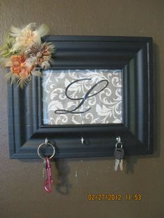 Custom key rack - so easy to make! Spray painted frame, scrapbook paper with big letter I traced onto it & then went over a couple of times with glitter glue. Screwed in a couple of small hooks in the bottom (also spray painted) and hot glued some scrapbook decorations on the top corner. Easy peasy! Original post I got the idea from linked to this post.