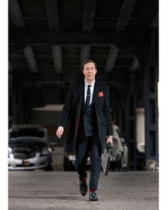 Pinstripe power suit. Red accents in suit, coat, and socks.