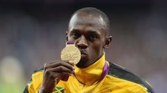 Gold medallist Usain Bolt of Jamaica poses on the podium during the medal ceremony for the men's 100m final on Day 10 at the Olympic