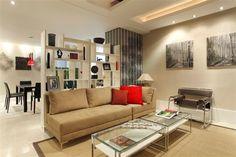Uma parede de nichos faz a divisória da sala de estar com a sala de jantar.