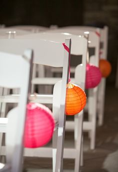 Small lanterns hanging from chairs- Pink and orange wedding