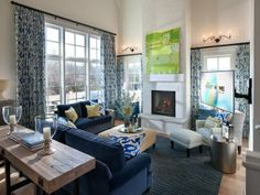 """Continue down the hallway from the foyer to be greeted with a soaring ceiling and an open floor plan in the great room.  To capture a clean, nontraditional approach, Linda Woodrum used a blue and white color palette. The fireplace acts as a sculptural feature, """"with a piece of art above the mantel that adds just the right wow.""""  http://hg.tv/v822"""