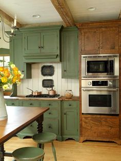 A Balanced Kitchen - funny as it may seem, I like the green cabinets better than I do the heavily grained wood ones. To me, the green ones 'feel warm' more cozy, homey, sit-down a spell, let's talk, if something spills, no biggie it's wash  wear. The others, I get a 'cold' feel from, we're more formal, better not spill anything. Hmmm...