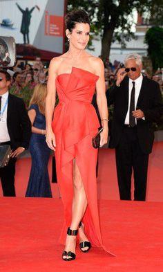 Para a abertura do 70º Festival de Veneza, a atriz Sandra Bullock desfilou um vestido vermelho tomara que caia com detalhes frontais e fenda, da grife J Mendel. O coque nos cabelos deixa o visual ainda mais elegante e as sandálias Roger Vivier combinam com a clutch também preta.
