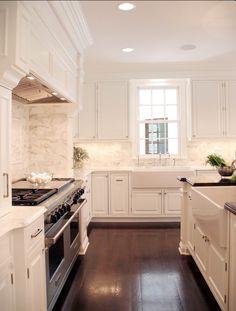 White marble backsplash, oversized cooktop and vent hood, farmhouse apron sink in front of the window