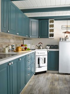 Corner stove and LOVE the color of the cabinets. I like the rustic floor with the modern cabinet look.