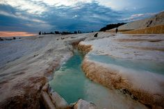 A hot spot on the backpacking trail and one of Turkey's most impressive natural wonders, the Pamukkale mineral spa, translated as 'cotton castle.' Stunning white terraces of calcium-rich warm waters spring up from the earth and cascade over low cliffs, forming the crisp, snow-like landscape.