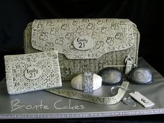 Handbag 21st Cake made to actual size. This is a replica of the birthday girl's birthday present.  x 4 cherry ripe mud cakes carved/filled/ganached/fondant/handpainted with her initials. Gumpaste accessories. The purse is LCMs (CRTs) ganached/fondant.