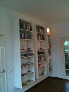 Ikea Billy bookcases mounted to the wall... I would love to do this with the glass doors for my dining room for china and glassware!