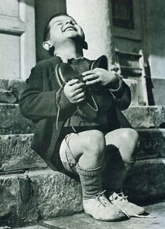 """JOY:  This photograph entitled """"Werfel's first pair of new shoes"""", appeared in the 1946 issue of Life magazine. Werfel, a six-year-old Austrian orphan, has just received his first new pair of shoes as part of the post-war relief effort of the American Red Cross."""