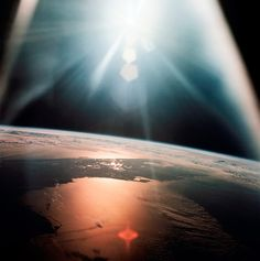 AS07-08-1933 was taken in 1968 from the Apollo 7 spacecraft—the first manned mission in the Apollo program—as it hovered 120 nautical miles above the Gulf of Mexico. Morning sunlight floods the sky and beams of light pour down over the Florida peninsula in the background.