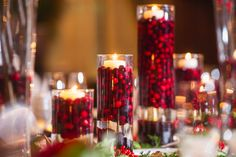 Christmas Wedding. cranberries, saran wrap, and distilled water to look like ice. make sure to use distilled water or bubbles will form inside the vase   I love candles, I also like the vertical nature of the display, rather than a flat display that grows outwards.  A rare exception to my theory that  red is an accent, not a color that can stand on it's own