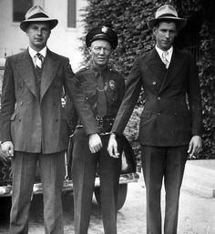 "Fullerton Patrolman Ernest E. Garner with bank robbers, Fullerton, 1927  Bank robbers W. Benjamin Morrison (left) and George Horine (right) of San Jose were captured when the car they were driving overturned at Spadra Rd. and Whiting Ave. The two 19-year-olds had robbed a bank in Saratoga, California the week before.    ""Don't tell my mother,"" said Morrison. ""She had carbon monoxide poisoning a couple of years ago and lost her memory. If she finds out about this it will give her a setback."""