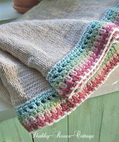 Neutral crochet blanket with color trim.