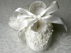 This shoe is made from a luxurious white dupioni silk fabric. Swarovski crystals and pearls accentuate the gorgeous Venice lace appliqués. An elegant satin ribbon bow adds the finishing touch