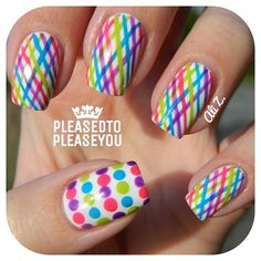 Gorgeous design on solid white nails with bright rainbow criss cross stripes of pink, purple, blue, green, accent thumb nails with polka dots