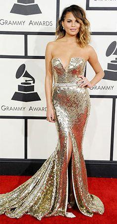 Chrissy Teigen wears a Johanna Johnson gold strapless, deep v fully sequined gown