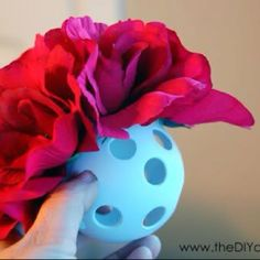 This is such a cute idea..use a plastic hockey ball u can find them at dollar store with fake flowers also found at dollar store, put hot glue around the inner part of holes in ball and stuff the flowers WITHOUT the stems into the hole and continue till all holes are filled and hang with a ribbon all around the desired room you choose :) enjoy crafting