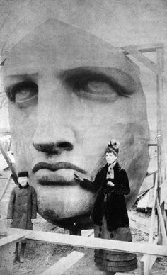 People posing next to the Statue of Liberty's face as it was being un-packed.