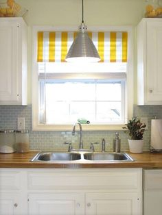 for the kitchen: white cabinets, wood countertops, gray walls, and a small yellow striped curtain