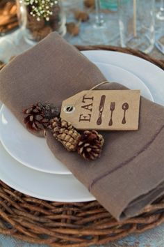 table setting with pine cones, brown and white, wicker charger