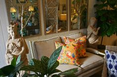 Loveseat vignette with colorfully patterned #toss #pillows and #garden #statues at Pot your garden gems in #colorful #vases at #Chicago #Mecox #interiordesign #MecoxGardens #furniture #shopping #home #decor #design #room #designidea #vintage #antique
