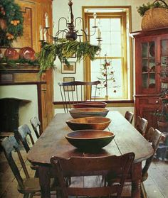 Simple Christmas Decorations, Antique Wood Bowls, Antique Farmhouse Table & Chairs, Redware Plates on the Mantle, A Feather Tree on the Window Ledge, Antique China Cabinet with a Egg Gathering Basket on top.