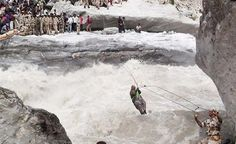 In this handout photograph received from the Indo Tibetan Border Police (ITBP) on June 24, 2013 members of the ITBP rescue stranded villagers along a rope bridge fixed across the Alaknanda river at Lambagad en route to Badrinath. Posted by floodlist.com #floods #uttarakhand