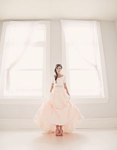 A blush skirted wedding dress with sleeves, pin tuck detailing, intricate, sparkly belt…and pockets!