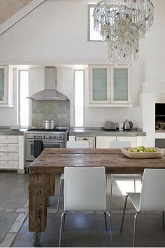 white walls, chandelier, wood table, hood, white chairs