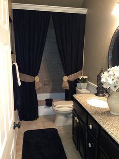 Use long drapes for shower curtain,crown molding to hide rod. Mauve curtains with gold rope to tie sides for guest bath upstairs.