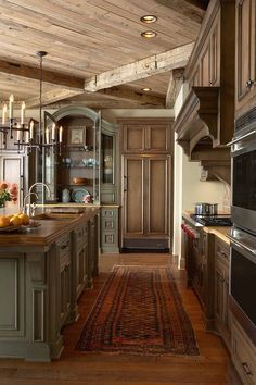Rustic Kitchen with wood counter on island and green painted cabinets