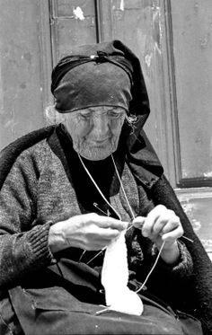 Old woman Knitting in Portugal. Notice how she has the yarn around her neck and a safety pin attatched to her shirt for tension. I one saw someone knitting like this. She was Greek. I've never tried it, but it seems like it would take some tension off your hands!