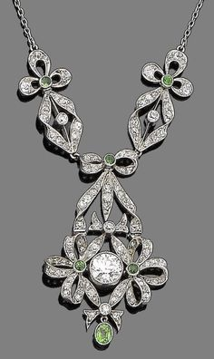 A demantoid garnet and diamond pendant necklace, circa 1905 The collet-set old brilliant-cut diamond within a finely pierced articulated surround of ribbon and knife-edge bar design set throughout with cushion-shaped and single-cut diamonds, highlighted with circular-cut demantoid garnets in collet-settings and suspending an oval-cut demantoid garnet drop, to a trace-link chain, principal diamonds approx. 0.75ct, remaining diamonds approx. 0.85ct total, lengths: pendant 3.9cm, chain 46.8cm