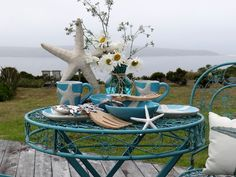 Love the turquoise snap of these starfish dishes and the wiry table and chairs, especially on the edge of the water!