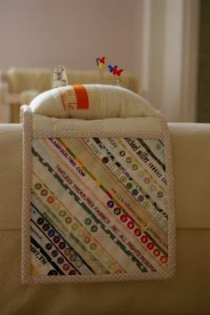 A sewing caddy stores your sewing stuff on the arm of a chair or couch